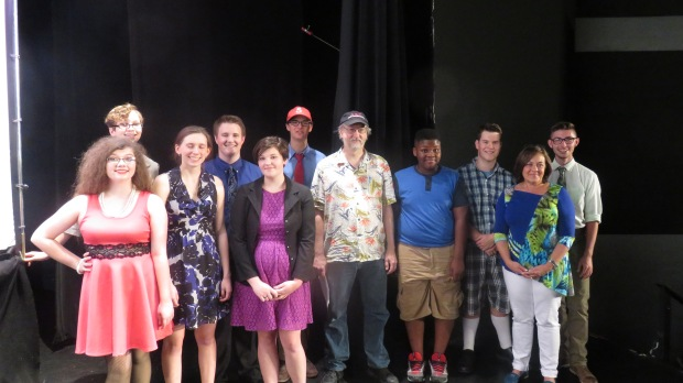 The cast of THE TALE OF THE WHALE. From left: Emily Wilkerson (in red, Cee Cee), Madi Wiley (behind her, the bureaucrat), Staley Lyle (Dee Dee) Camden Mahan (mayor), Gabby Wyatt (reporter), Whit Whitfield (Ernie), the playwright, Jacob Breedlove (kid), Caleb Mahan (Old Man McGrump), director Mimi Grubb, Blake Mitchell (Larry).