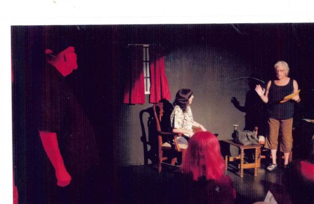 The ghost of Bert looks on as his widow, Sally, interacts with a visiting nurse.